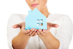 Businesswoman holding a blue paper house Royalty Free Stock Photos