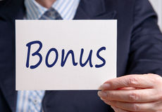 Businesswoman holding bonus sign. Businesswoman holding large card with hand written bold blue text ' bonus stock images