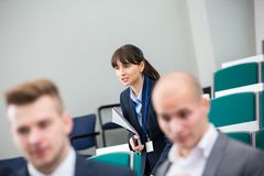 Businesswoman Holding Book While Standing In Lecture Hall stock images