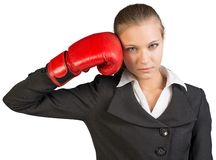 Businesswoman holding boxing glove at her temple Stock Photos