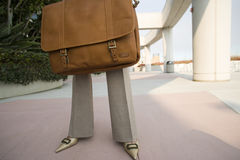 Businesswoman holding briefcase, low section, front view Stock Images