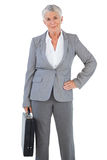 Businesswoman holding briefcase and putting her hand on hip Royalty Free Stock Images