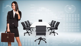Businesswoman holding briefcase and showing thumb-up Royalty Free Stock Photos