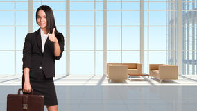 Businesswoman holding briefcase and showing thumb- Stock Photos