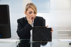 Businesswoman holding broken digital tablet Royalty Free Stock Images