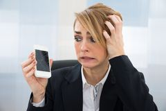 Businesswoman holding broken smartphone. Close-up Of Worried Businesswoman Holding Broken Screen Smartphone In Office stock images