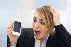 Businesswoman holding broken smartphone. Close-up Of Worried Businesswoman Holding Broken Screen Smartphone In Office royalty free stock images