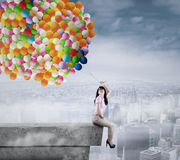 Businesswoman holding a bunch of balloons Royalty Free Stock Images