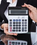 Businesswoman holding calculator at desk Stock Image