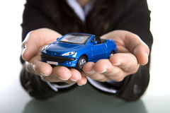 Businesswoman holding car in the hands. Insurance or car business concept