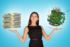 Businesswoman holding cash and earth globe Stock Photography