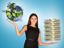 Businesswoman holding cash and earth globe Stock Images