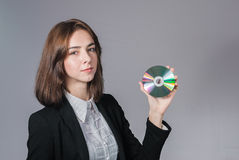 Businesswoman holding the cd disk in her hand. Portrait of businesswoman holding the cd disk in her hand isolated on white Stock Photography