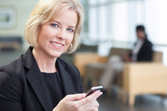 Businesswoman holding cell phone Stock Images