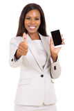 Businesswoman holding cell phone. Pretty businesswoman holding cell phone and giving thumb up Royalty Free Stock Images
