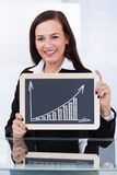 Businesswoman holding chalkboard with chart Stock Photos