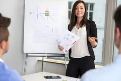 Businesswoman Holding Chart While Communicating With Colleagues stock photography