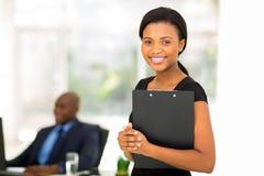Businesswoman holding clipboard. Beautiful businesswoman holding clipboard with colleague on background Stock Photo