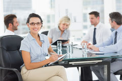 Businesswoman holding clipboard with colleagues discussing in office Stock Photography