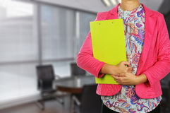 Businesswoman holding clipboard in meeting room Stock Photo