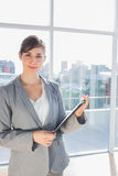 Businesswoman holding clipboard and smiling at camera Royalty Free Stock Images