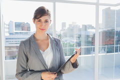 Businesswoman holding clipboard and smiling Stock Photos