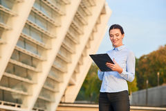 Businesswoman holding clipboard and smiling. Stock Photography