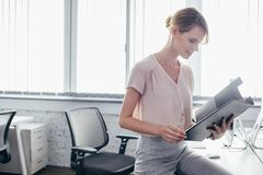 Businesswoman holding clipboard. Smiling young businesswoman holding clipboard in office Stock Images