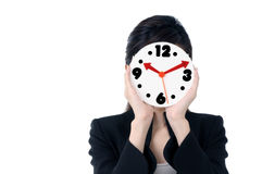 Businesswoman holding clock over her face Stock Photos