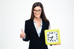 Businesswoman holding clock and showing thumb up Royalty Free Stock Images