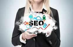 Businesswoman is holding a cloud as a metaphor of 'SEO' Royalty Free Stock Image