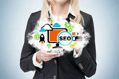 Businesswoman is holding a cloud as a metaphor of 'SEO' Stock Images