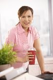 Businesswoman holding coffee cup. Businesswoman standing at desk holding coffee cup, looking at camera, smiling Royalty Free Stock Images