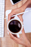 Businesswoman holding coffee cup and pen Royalty Free Stock Images