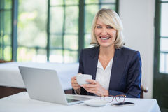 Businesswoman holding coffee cup in a restaurant. Portrait of businesswoman holding coffee cup in a restaurant Stock Photos