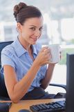Businesswoman holding coffee mug and smiling Stock Image