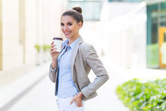 Businesswoman holding coffee outdoors Stock Image