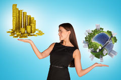 Businesswoman holding coins and earth globe Stock Photos
