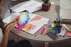 Businesswoman holding colour swatch at office desk Royalty Free Stock Photos