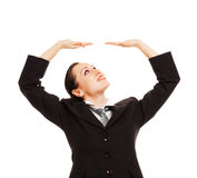 Businesswoman holding copyspace and looking up Stock Photos