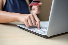 Businesswoman holding credit card for online shopping while making orders via the Internet. business, technology, ecommerce and stock photo