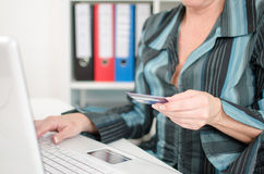 Businesswoman holding a credit card and typing on a keyboard Royalty Free Stock Photos
