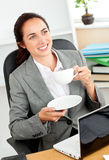 Businesswoman holding cup of coffee in her office Stock Photography
