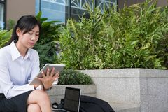 Businesswoman holding digital tablet & coffee outside office bui Stock Photo