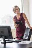 Businesswoman Holding Digital Tablet At Desk Royalty Free Stock Photo