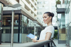 Businesswoman holding a digital tablet in hands outdoors Stock Photos