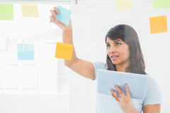 Businesswoman holding digital tablet and sticky notes Stock Image