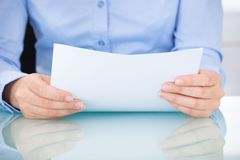 Businesswoman holding documents at desk Royalty Free Stock Photo