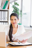 Businesswoman holding documents at desk Stock Photo