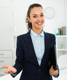 Businesswoman holding documents in hands in office. Successful and confident businesswoman holding documents in hands in office Royalty Free Stock Images